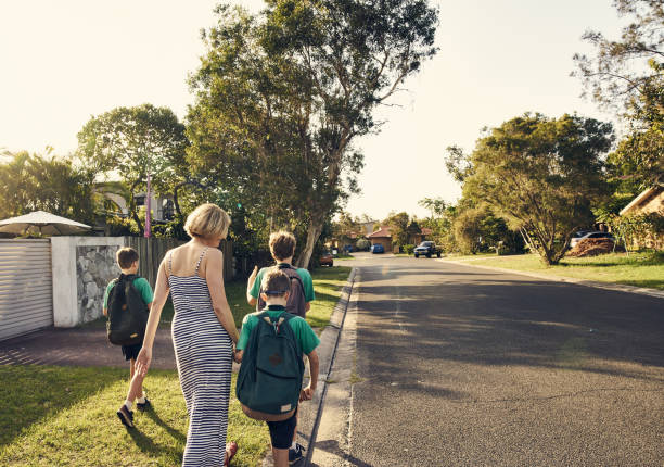 Shot of a mother walking three boys to school